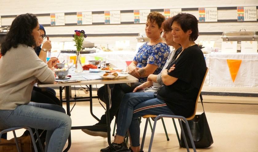 Deelnemers en een landelijk ambassadeur van het Nationaal Integratie Diner.