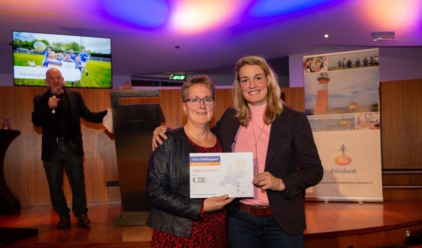 Een lid van KV Stormvogels krijgt de cheque uit handen van Edith Bosch.