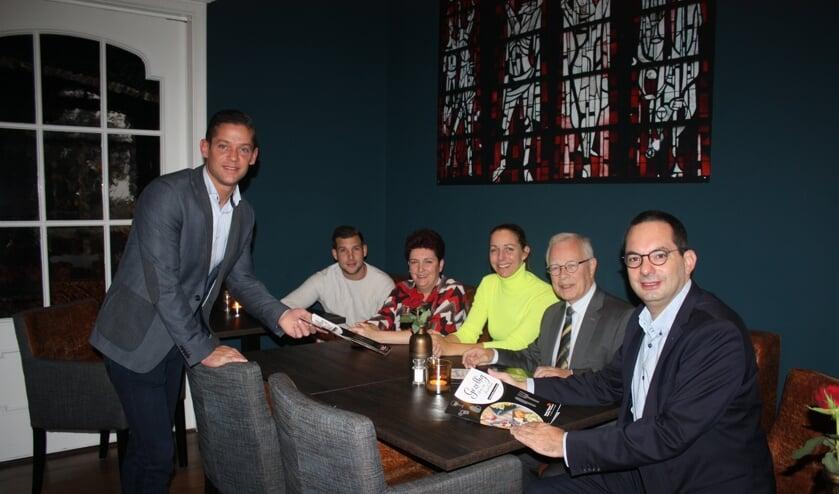 Ruud de Weert overhandigt een brochure aan collega-horecaondernemers, wethouder Kielman en burgemeester Adriaansen.