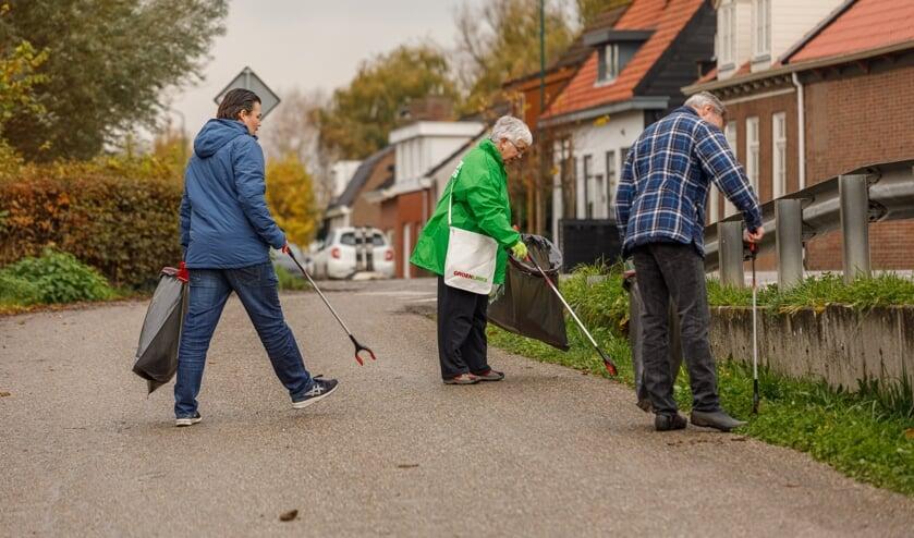 Vrijwilligers prikken samen afval op. FOTO MARIETTE KAPITEIN