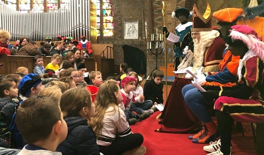 Kinderen zouden het liefst allemaal op schoot kruipen, als Sinterklaas vertelt tijdens de gezinsviering in de Lourdeskerk.