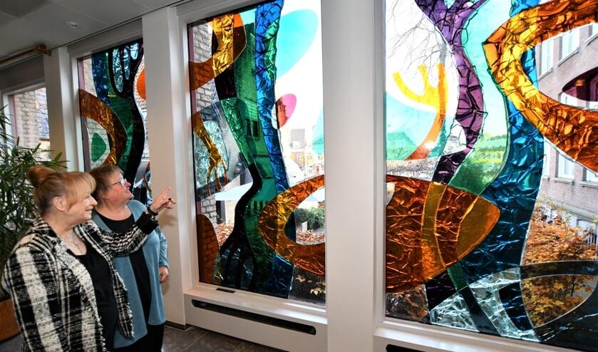 Annette Gefkens (r) en Julia Bakker twee leden van de werkgroep voor het glas appliqué in de Schonckzaal van het gemeentehuis in Etten-Leur. FOTO FRANS VAN DER BOM
