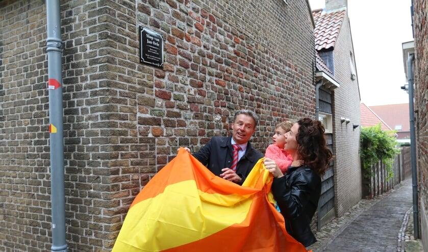 Willemien en Zoë Mallekote onthullen op de muur van hun huis, samen met burgemeester Huub Hieltjes het bordje van 'het slop van Jan Oele'.