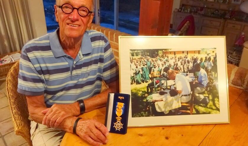 Bert Slingenberg met zijn onderscheiding en een foto van zijn ontwikkelingswerk.