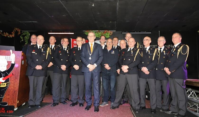 De gedecoreerde brandweerlieden poseren met burgemeester Ruud van den Belt.