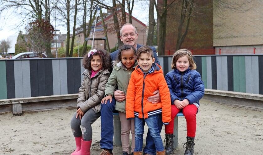 <p>Rinus Voet met een paar kinderen van Montessorischool De Basis, &eacute;&eacute;n van de dertien scholen van Prisma.&nbsp;</p>