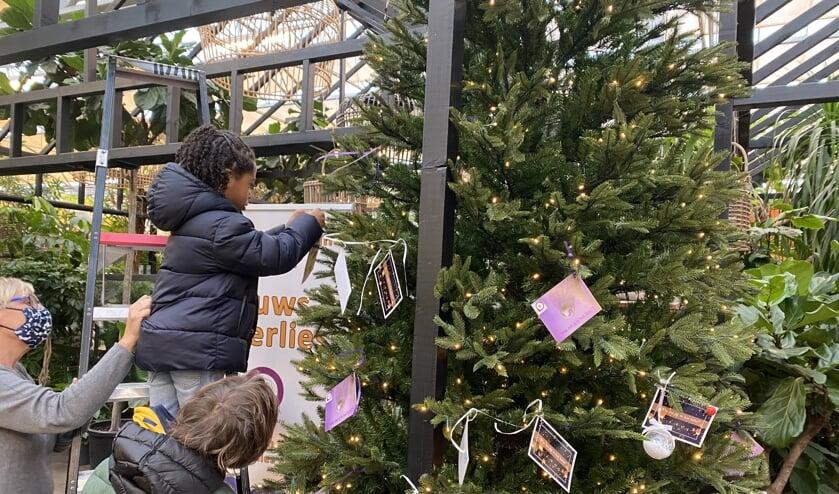 Kinderen hangen een wens in de kerstwensboom.