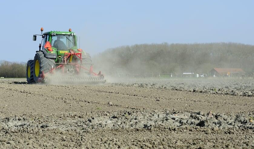 Een boer aan het werk op het land bij Ritthem.
