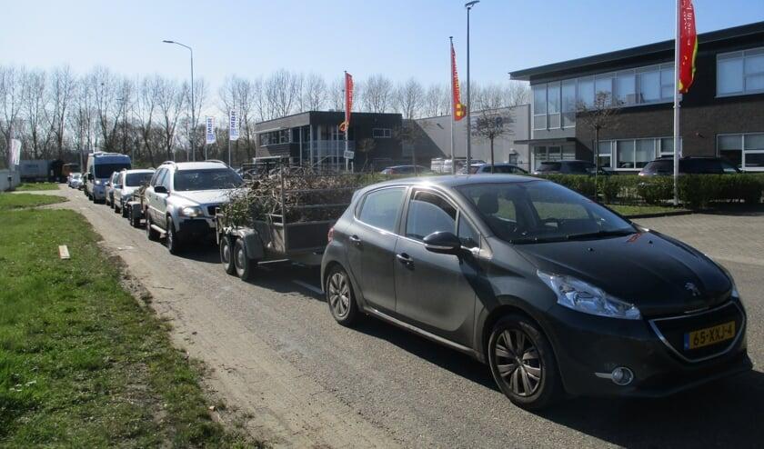 Een lange rij van automobilisten bij de milieustraat.