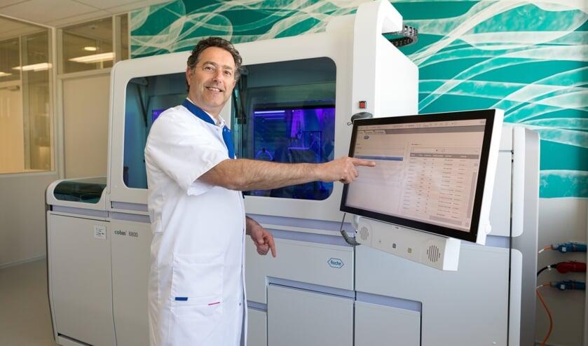 Arts-microbioloog Bram Diederen bij de nieuwe machine waarmee meer en sneller getest kan worden op het coronavirus.