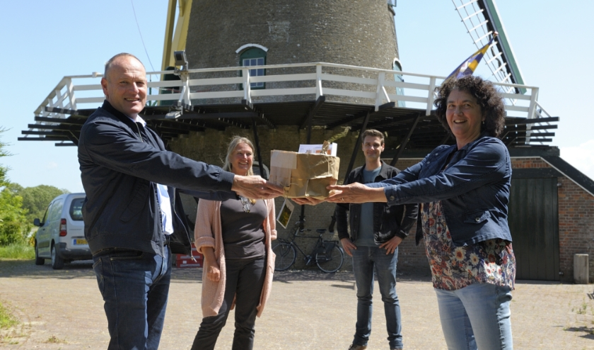 Chris Maas neemt het eerste pakketje in ontvangst uit handen van de initiatiefnemers.