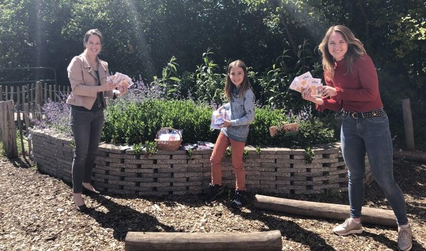 Joyce Verwijs van boekhandel Dieleman (l) reikt op het Natuurplein de boekenbonnen uit aan Kaya Dekkers en juf Carmen Bastiaanse.