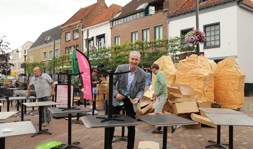 Wethouder Willy Knop steekt een handje toe bij de bouw van het megaterras op de Markt in Steenbergen.