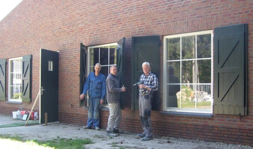 Leden van de vrijwilligersploeg plaatsen luiken aan de voorzijde van De Karkooi.