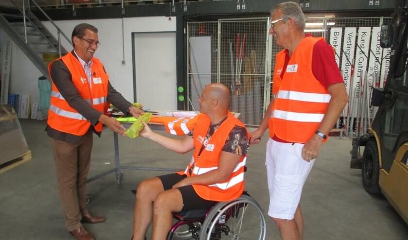 Marijn Koevermans ontvangt van wethouder Van Dorst de spullen die hem moeten helpen bij het weghalen van zwerfvuil.