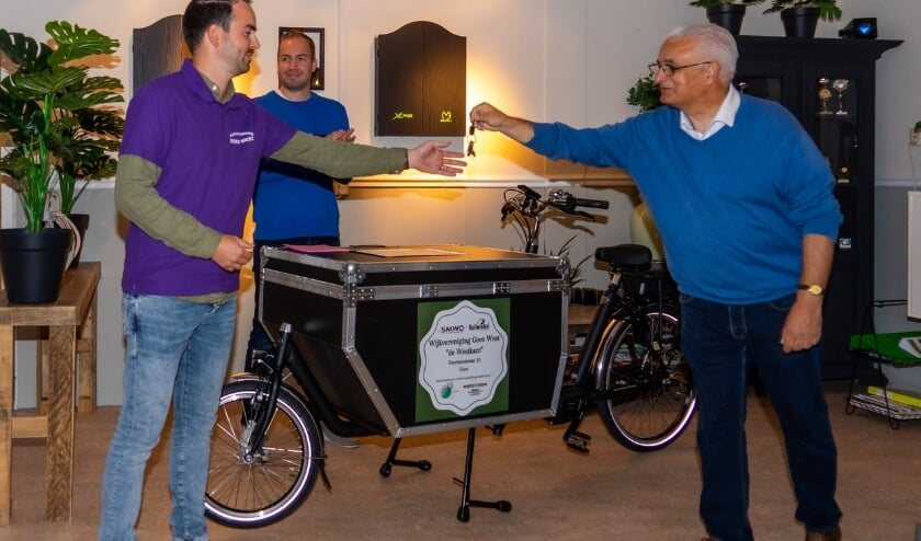 Yannick de Potter, van de wijkvereniging, ontvangt de fietssleutel van Rien Heijboer van SOMV. Op de achtergrond Joost de Goffau de wijkwethouder.