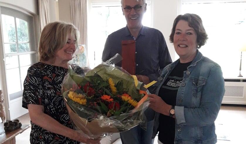 Voorzitter Maria van Nispen overhandigt de jubilaris een boekt bloemen.