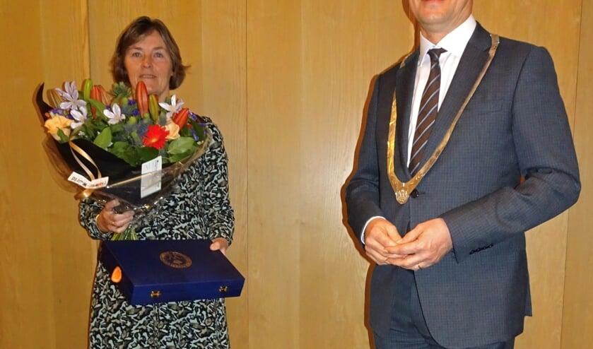 <p>Marleen Poortvliet krijgt het lintje en bloemen van burgemeester Bas van den Tillaar.</p>