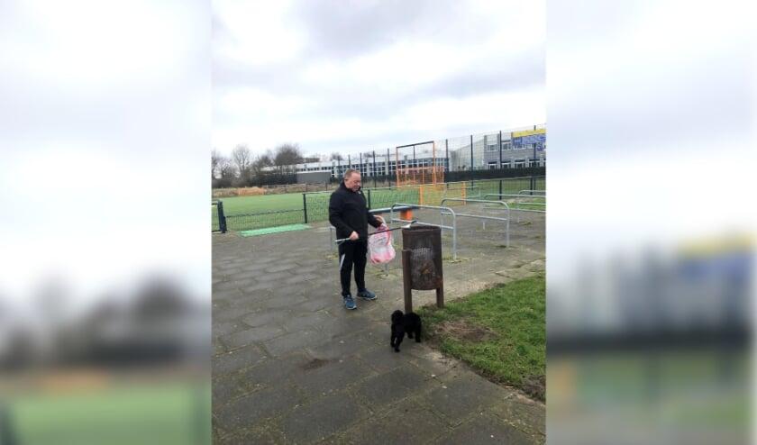 <p>Henk Schotanus laat zijn hondje Pip uit en ruimt meteen rommel op.</p>