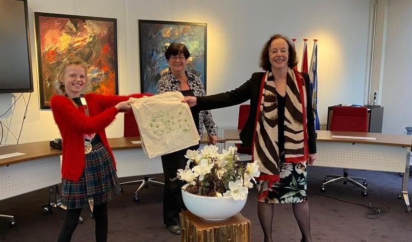 <p>Kinderburgemeester Mares overhandigt een van haar zelfontworpen tassen aan burgemeester Loes Meeuwisse. Op de achtergrond wethouder Anja Slenter.</p>