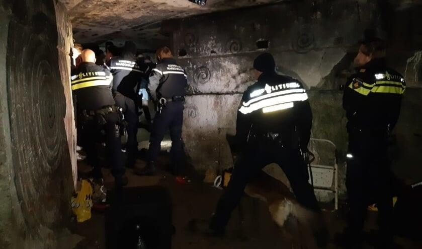 Agenten gaan met politiehonden de bunker in.