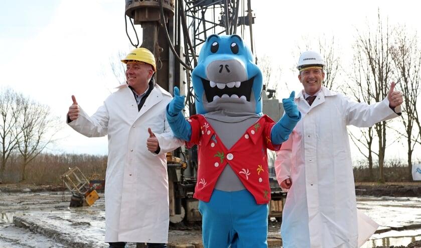 Wethouder Jon Herselman (r), directeur Hans Moors van bouwbedrijf Vaessen en de mascotte zijn blij dat de bouw kan beginnen.