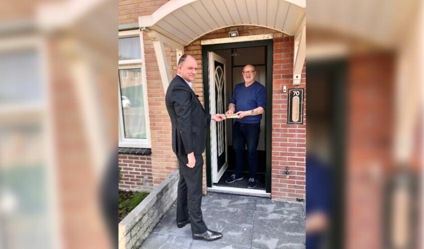<p>Wethouder Kees Verburg overhandigt een kookboek aan een matelzorger.</p>
