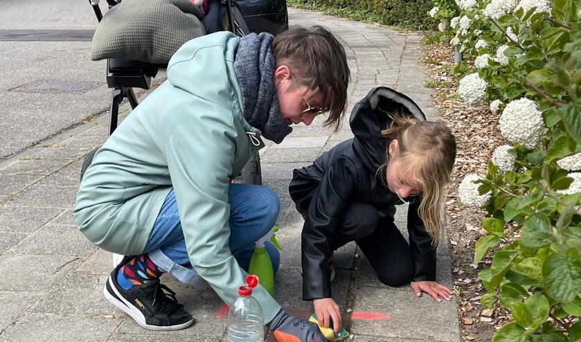 Anna-Maria Nooy poetst samen met haar dochter twee struikelstenen in Park de Griffioen in Middelburg